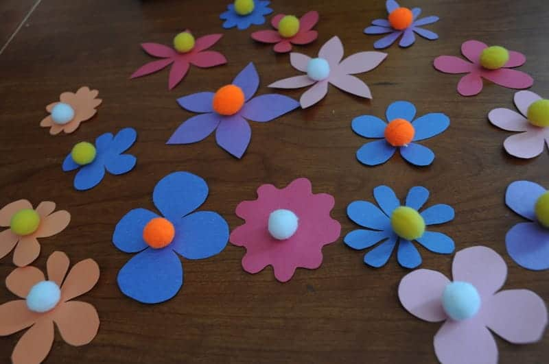 Add pom poms in the center of the flower cutouts