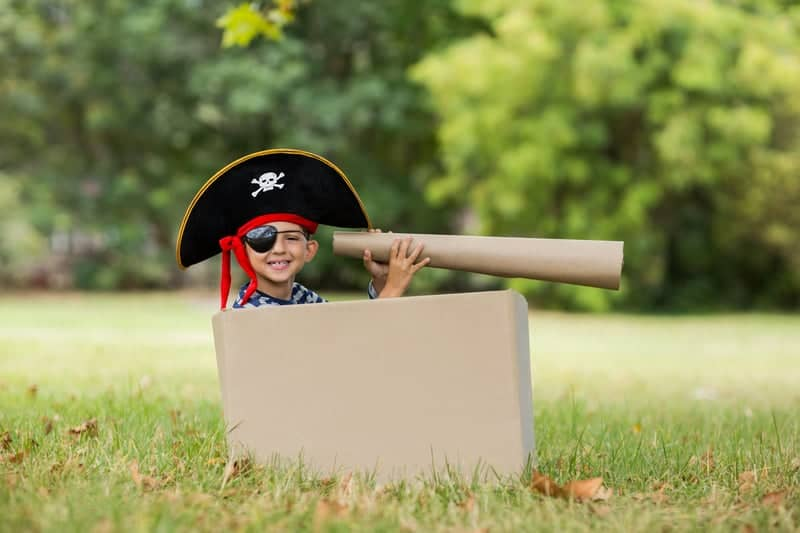 Pirate boy decked out with a pirate hat, pirate eye patch and a pirate telescope