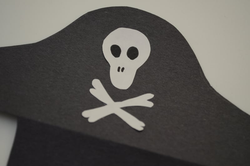 Cut out a skull and two bones from white construction paper